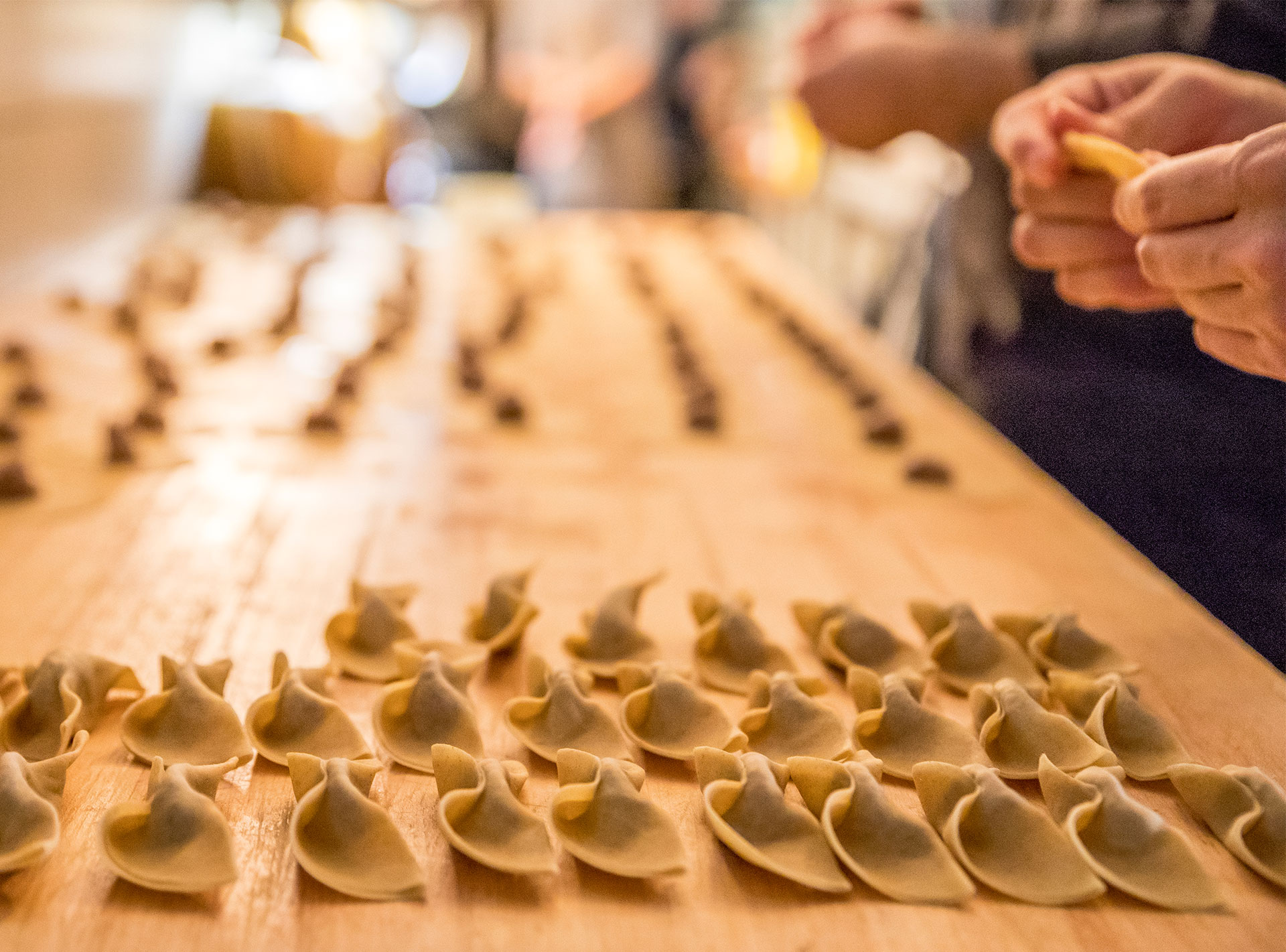 Handmade pasta being crafted at a wooden table in its fresh state